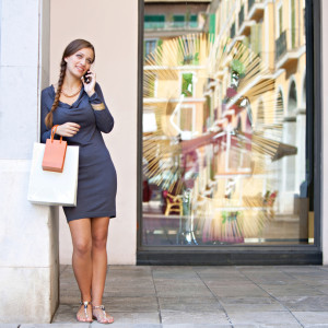 Stylish and beautiful elegant young woman carrying shopping bags and leaning on a column using her smartphone cell to make a call while in a luxurious shopping mall, lifestyle. Consumerism and technology.