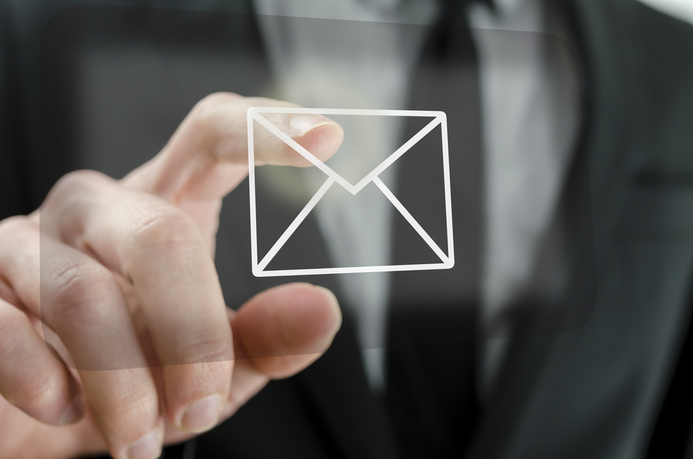Businessman touching email icon on a virtual screen.