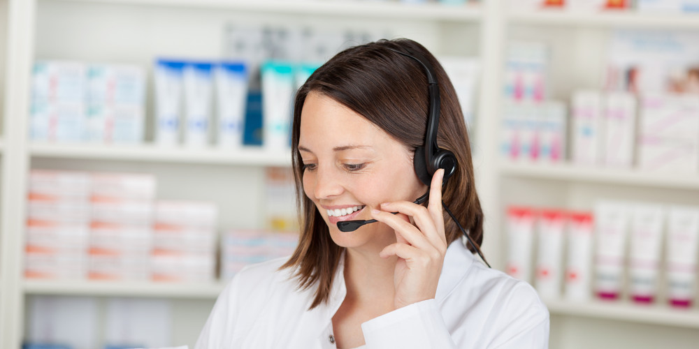 Happy mid adult female pharmacist conversing on headset in pharmacy