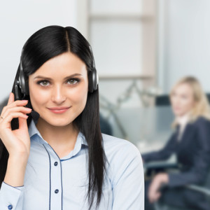 Front view of the smiling brunette support phone operator with headset. Office workplace background in blur.