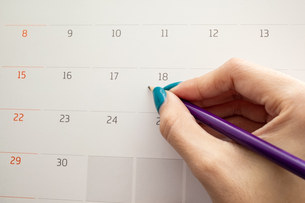 hand holding pencil on calendar for  making appointment  important day
